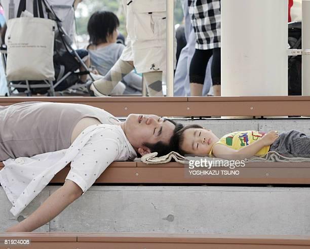 Father and his son take a nap on a bench at an interval of a sea animal show at the Hakkeijima Sea Paradise aquarium at Yokohama city in Kanagawa...