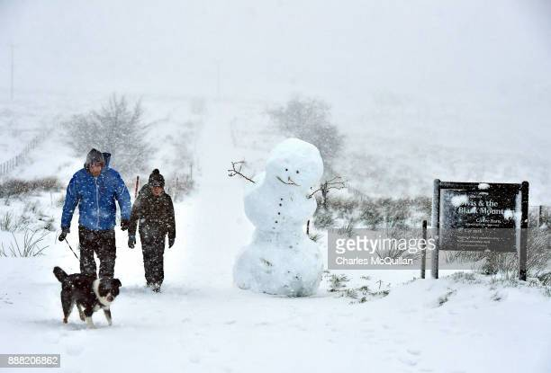 A father and his son walk their dog past a large snowman on Black mountain on December 8 2017 in Belfast Northern Ireland The MET Office has issued a...