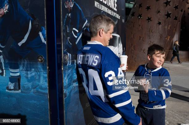 A father and his son wearing the same Leafs Jersey take in the late day sun before the regular season NHL game between the Montreal Canadiens and the...
