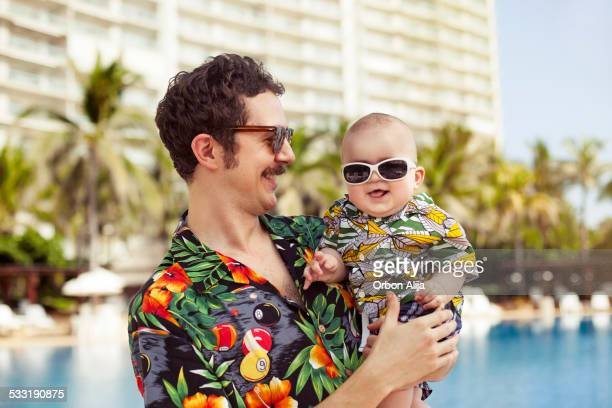 father and his son with hawaian shirts - hawaiian shirt stock photos and pictures