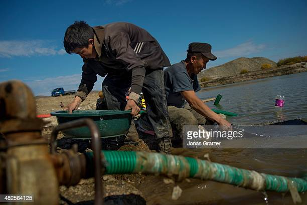 Father and his son work hard to pan and sieve for gold from the extracts of soil taken from underground in the Sharygol district of Mongolia....