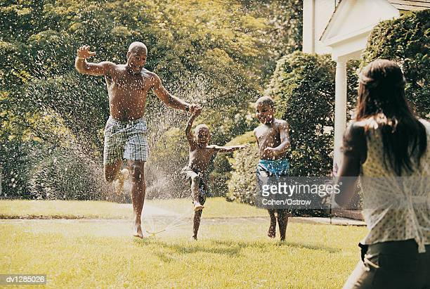 father and his sons running through a water sprinkler in a garden and their mother watching - barefoot black men stock pictures, royalty-free photos & images