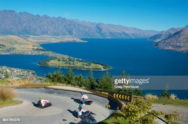 father and his three children riding skyline luge cars on bob's peak, high above lake wakatipu. - the remarkables stock-fotos und bilder