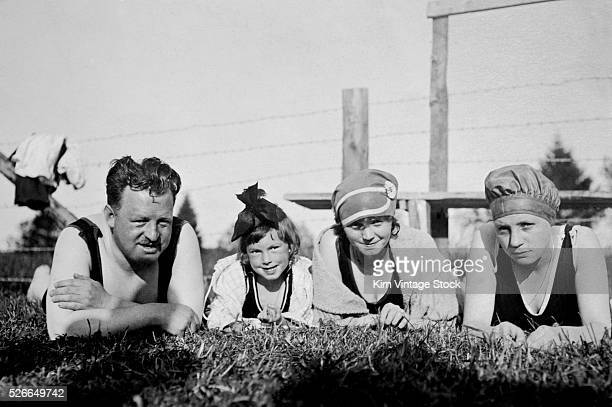 A father and his three daughters lay in the grass for a group portrait with their swimming suits on
