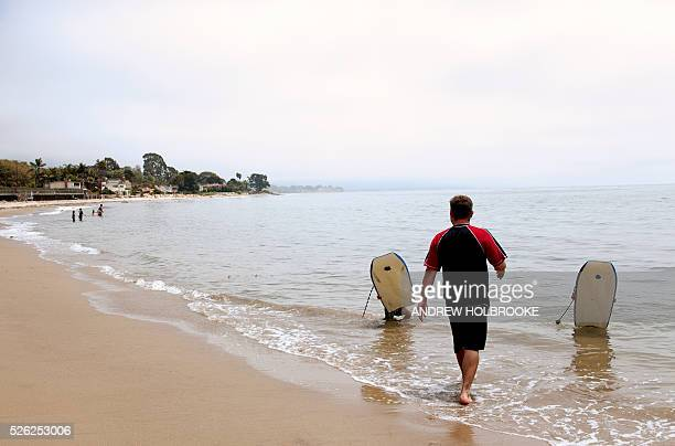 A father and his two children on Miramar Beach on the Pacific Ocean Children with boogy boards Montecito is a wealthy beach community along...