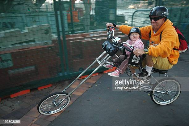CONTENT] A father and his very young daughter are riding along on a motorcycle styled chopper bicycleBoth are smilingThe young child is seated on a...