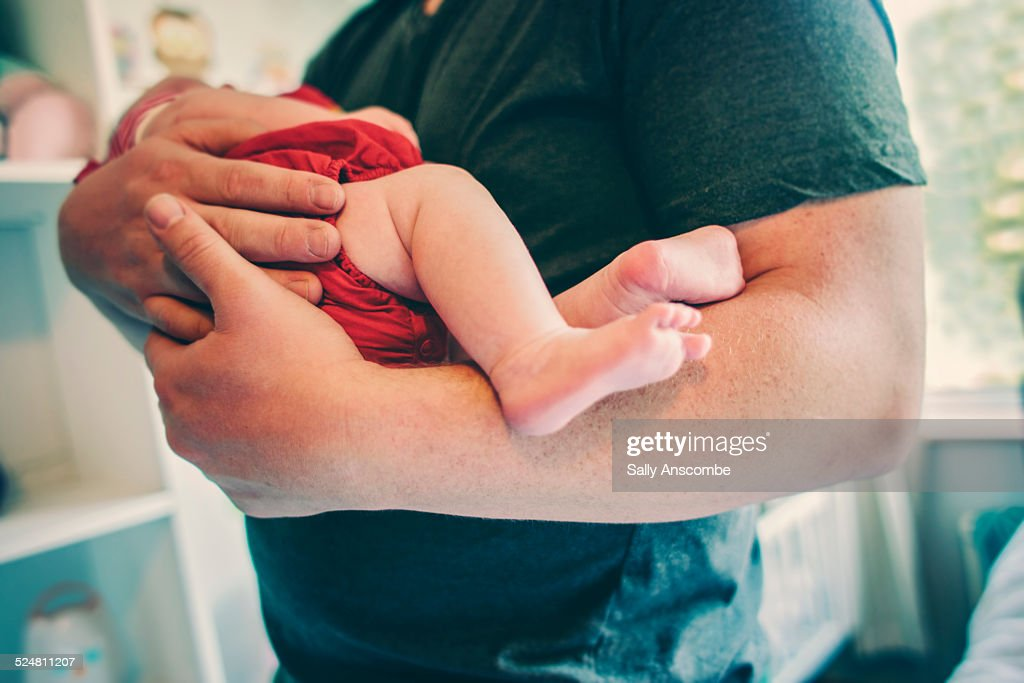 Father and holding his newborn baby girl : Stock Photo
