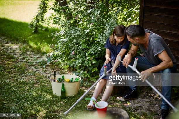father and injured daughter sitting together at garden shed - crutches stock photos and pictures