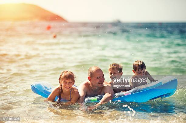 Father and kids having fun in sea on air bed