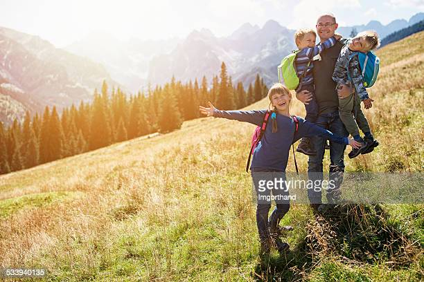 Father and kids hiking in the mountains