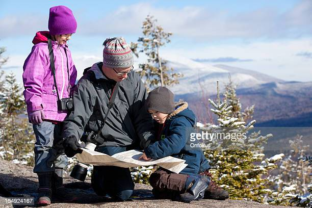 Father and Kids Looking at Map on Mountain Summit