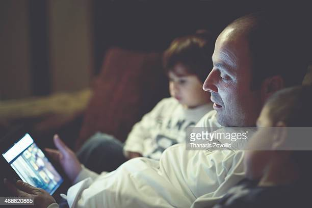 father and kids looking at tablet - mid adult men stock pictures, royalty-free photos & images