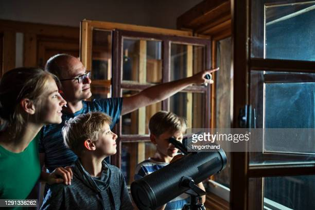 father and kids observing the moon and the stars - astronomy stock pictures, royalty-free photos & images