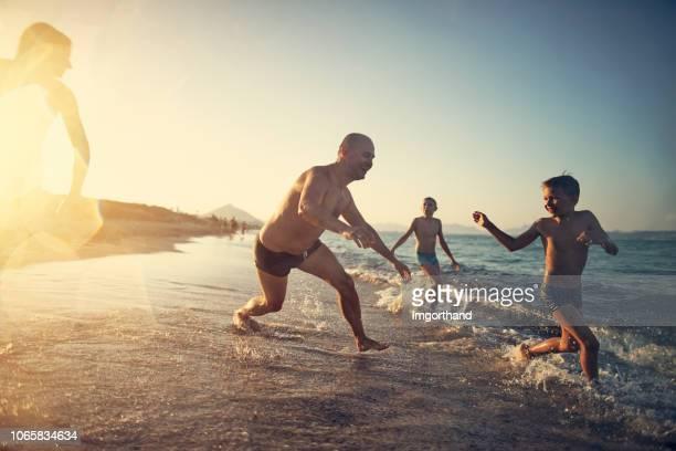 父とタグをビーチで遊ぶ子供たち - kids playing tag ストックフォトと画像