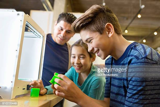 Father and kids printing 3D objects with 3D printer