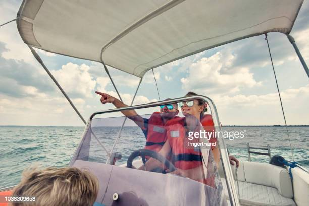 père et enfants circonscription un bateau sur le lac de garde - transport nautique photos et images de collection