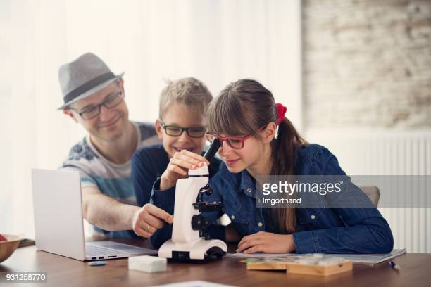 Father and kids using microscope at home