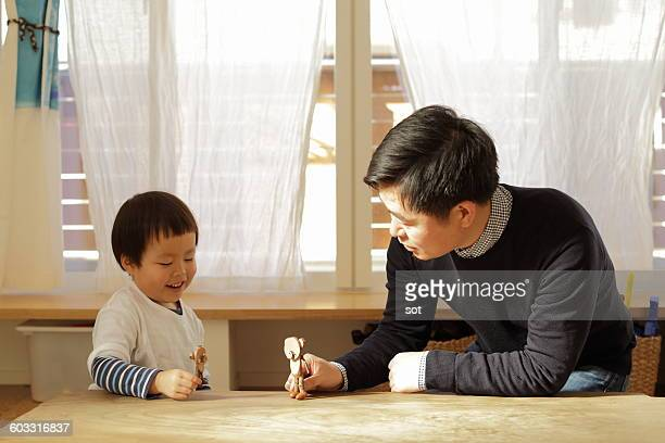 Father and little boy playing wooden toys
