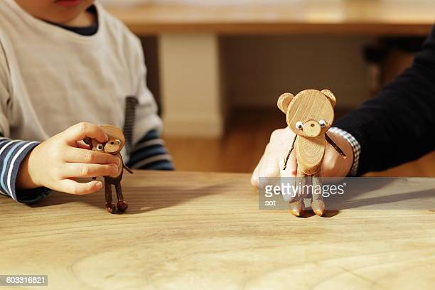 Father and little boy playing wooden toys,close up