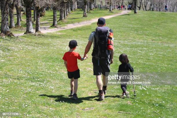 father and little children hiking in urbia, basque country. - padre soltero fotografías e imágenes de stock