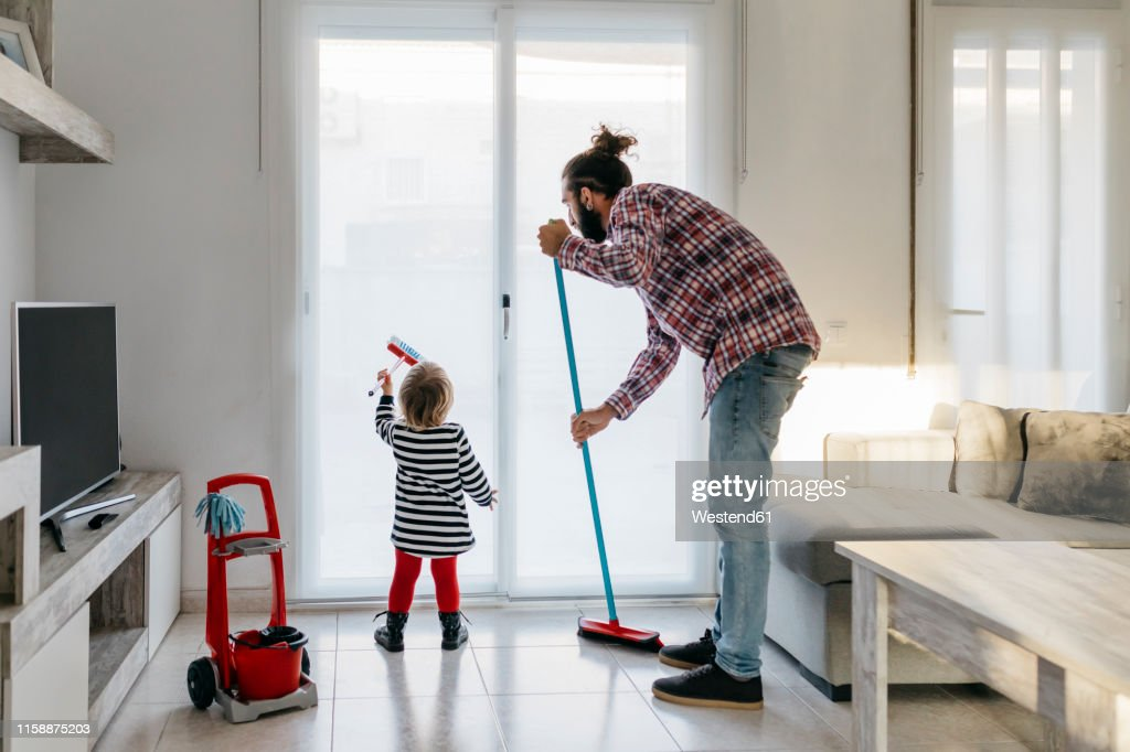 Father and little daughter cleaning the living room together : Stock Photo