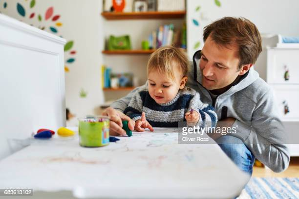Father and little daughter drawing together