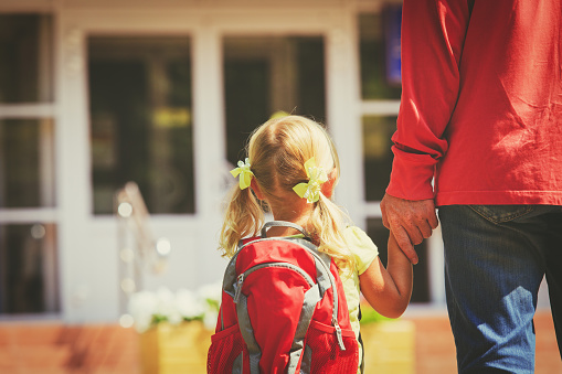 father and little daughter go to school or daycare 826736252