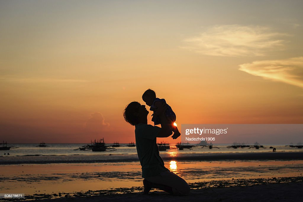 father and little daughter on sunset beach : Stockfoto