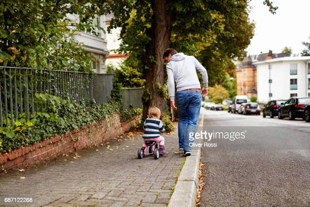 Father and little daughter on tricycle on pavement