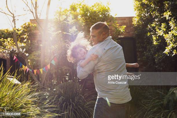 father and little daughter's happy jumping moments in garden - リアルライフ ストックフォトと画像