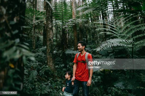 Father and little girl hiking in jungle