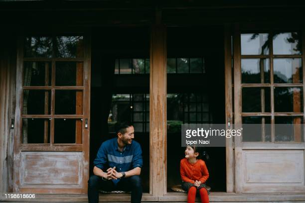 father and little girl sitting on patio and smiling at each other - 長野県 ストックフォトと画像