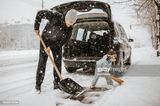 father and little son cleaning snow around car - digging stock pictures, royalty-free photos & images
