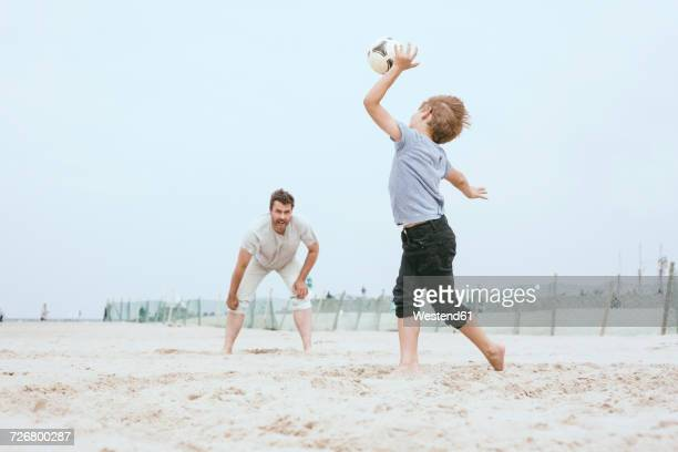 Father and little son playing with ball on the beach