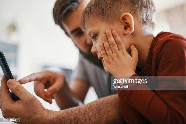 father and little son with smartphone - expliquer photos et images de collection