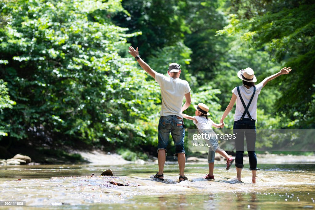 Father and mother and daughter play in the river : Stock Photo