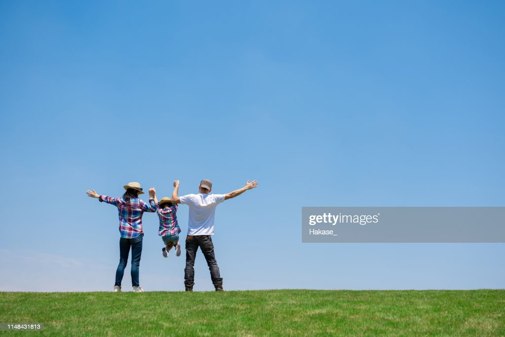Father and mother and daughter playing in the meadow : Stock Photo