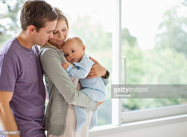 Father and mother embracing t heir baby boy (6-11 months)