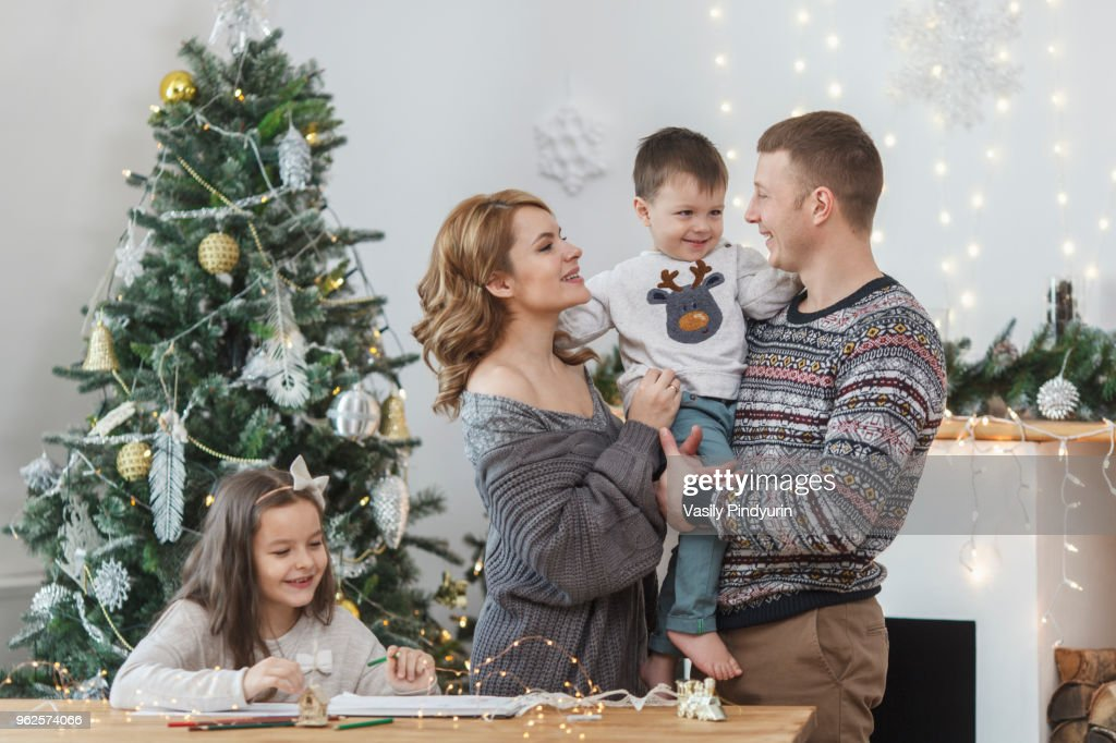 Father and mother holding son by daughter sitting at table against Christmas tree : Stock Photo