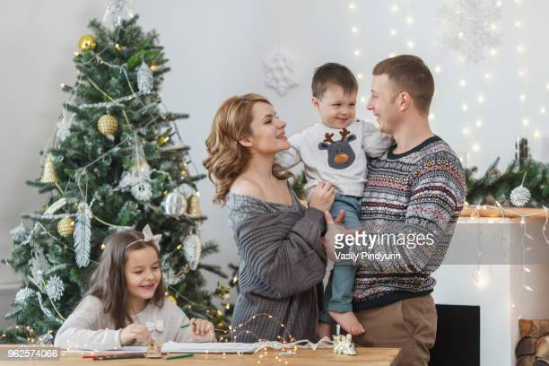 Father and mother holding son by daughter sitting at table against Christmas tree