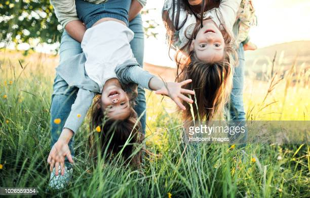a father and mother holding their daughters upside down outside in spring nature. - frühling stock-fotos und bilder
