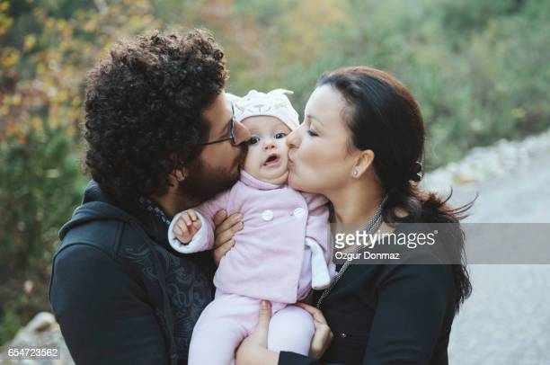 Father and mother kissing babygirl
