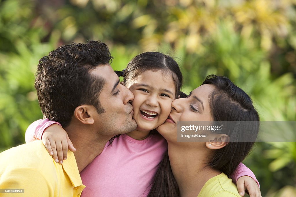 Father and mother kissing daughter (6-7) outdoors : Stock Photo