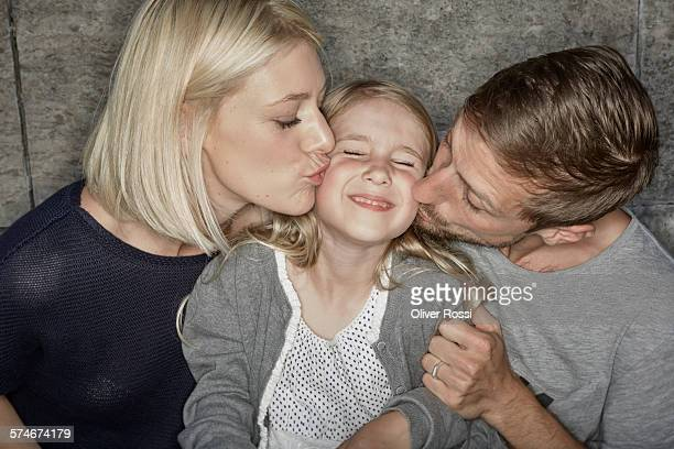 father and mother kissing daughter - famiglia con figlio unico foto e immagini stock