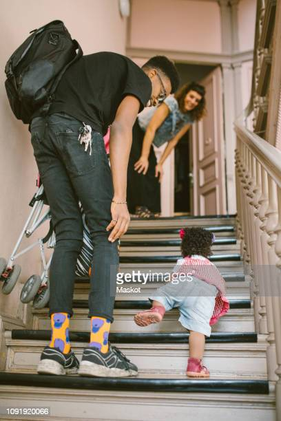 father and mother looking at baby girl climbing steps in apartment - stay at home father stock pictures, royalty-free photos & images