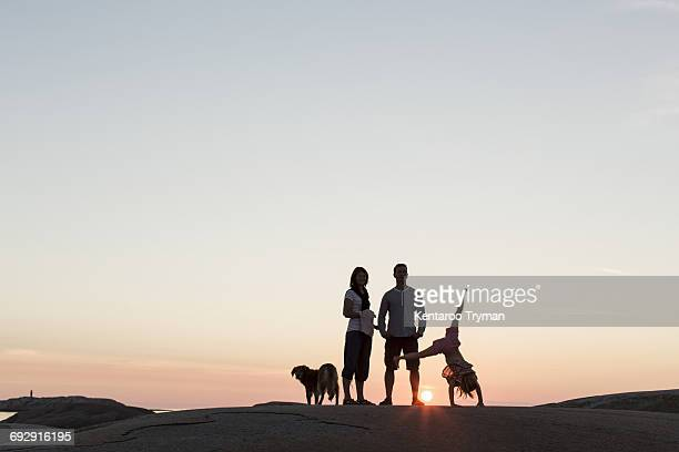 Father and mother looking at girl performing cartwheel on rock formation against sky during sunset