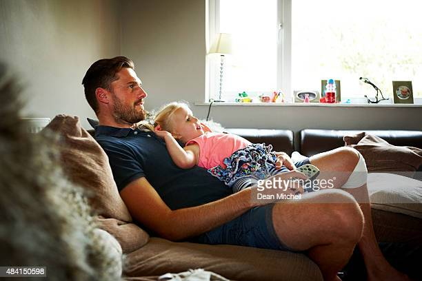 father and mother on sofa watching television - family watching tv stock pictures, royalty-free photos & images