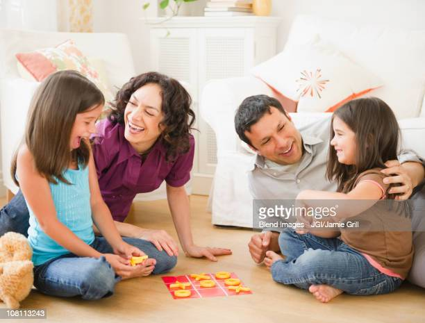 Father and mother playing game in livingroom with children