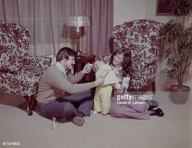 father and mother playing with baby girl in living room  - {{relatedsearchurl(carousel.phrase)}} fotografías e imágenes de stock