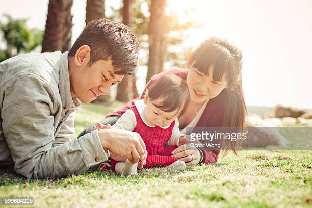 Father and mother playing with baby girl in park